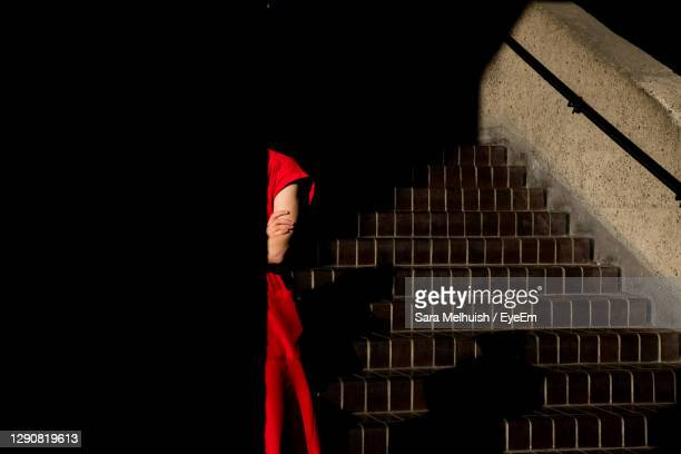 lady in red in shadows by staircase - architecture stock pictures, royalty-free photos & images