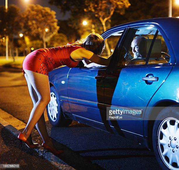 Lady in red: young prostitute negotiates with eager car driver