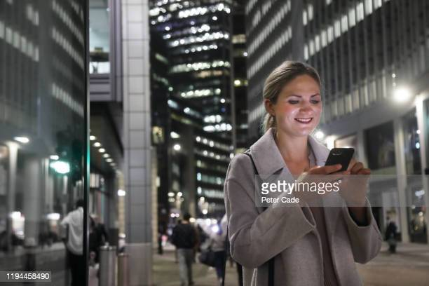 lady in the city at night with her phone - cream coloured blazer stock pictures, royalty-free photos & images