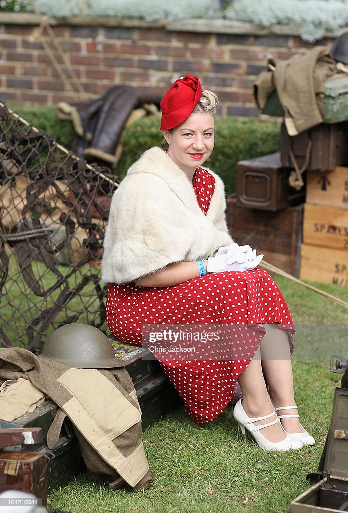 A lady in vintage clothing poses for a photograph during Goodwood Revival 2010 at Goodwood on September 17, 2010 in Chichester, England. The event is based around a classic car race meeting and airshow but celebrates all things 1945 until 1966.