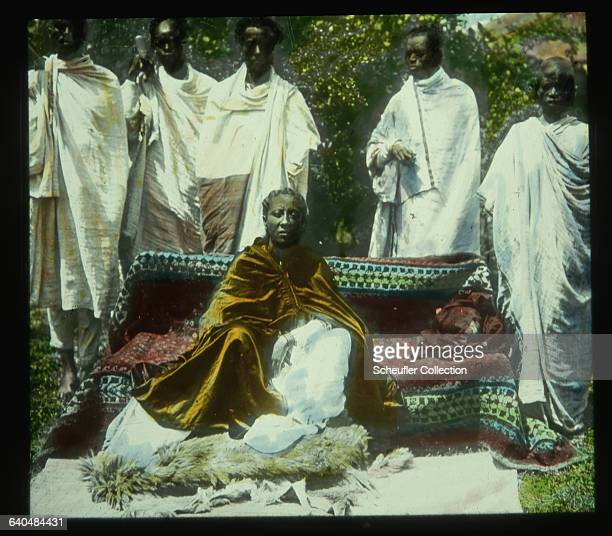A lady in waiting of the Ethiopian royalty poses on a sofa accompanied by several servants and bodyguards