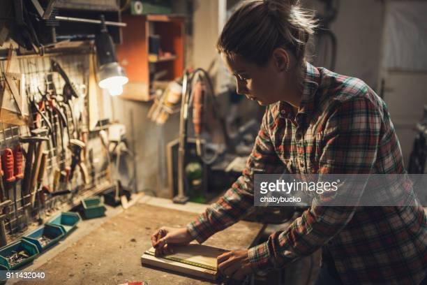 Lady in workshop measures wooden board