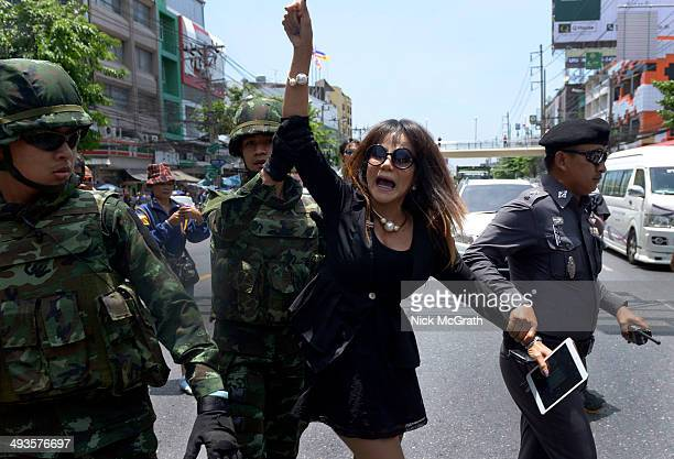 A lady is escorted by military officers and a policeman after a confrontation with anti coup protestors on May 24 2014 in Bangkok Thailand Protestors...