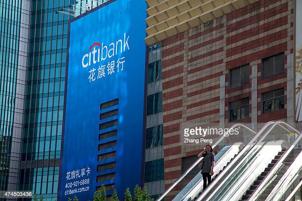 A lady is taking escalator downstairs before the huge billboard of Citibank