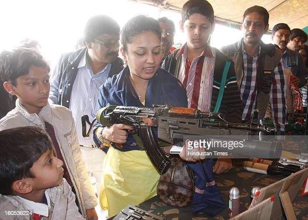 A lady is trying her hand at an Assault Rifle fitted with Grenade Launcher during 'Army Equipment Display and Military Tattoo' at Army Polo Ground...