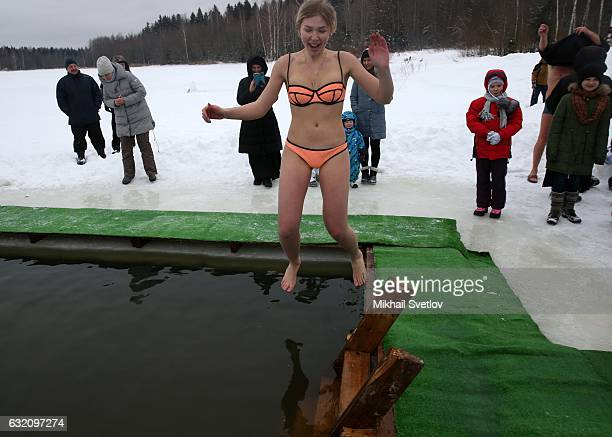 A lady jumps into the icy cold water while celebrating the Epiphany church holiday in the village Kholmy on January 19 50 km west of Moscow Russia...