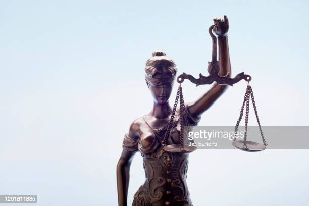 lady justice against blue background - crime or recreational drug or prison or legal trial stock-fotos und bilder