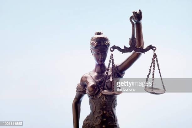 lady justice against blue background - justizwesen stock-fotos und bilder