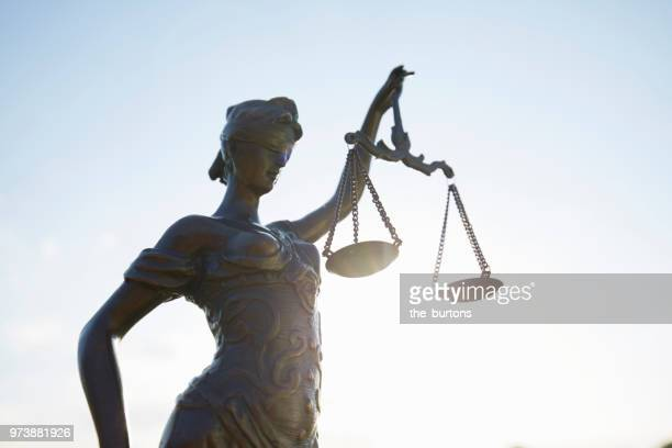 lady justice against clear sky - justice photos et images de collection