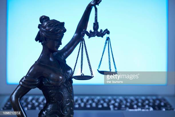 lady justice against laptop monitor - lady justice stock pictures, royalty-free photos & images