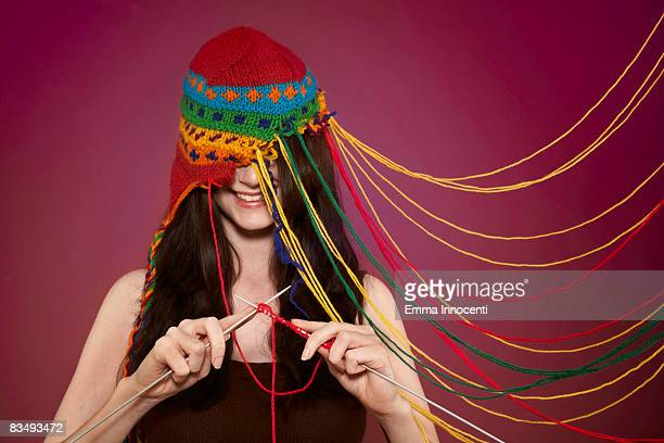 lady knitting on her own hat - multi colored hat stock pictures, royalty-free photos & images