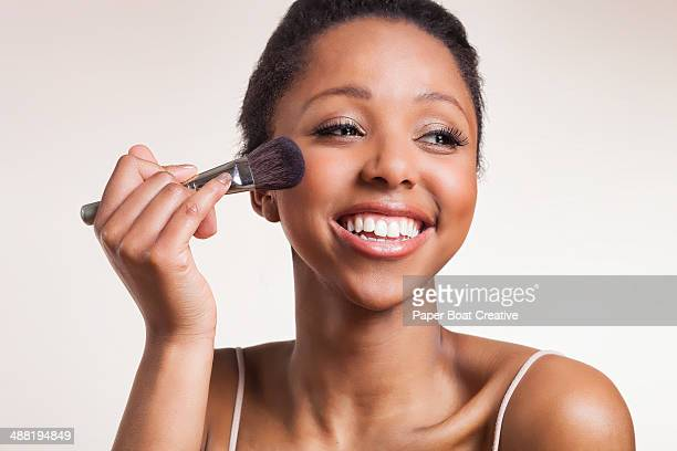 Lady laughing while applying blush brush on cheeks