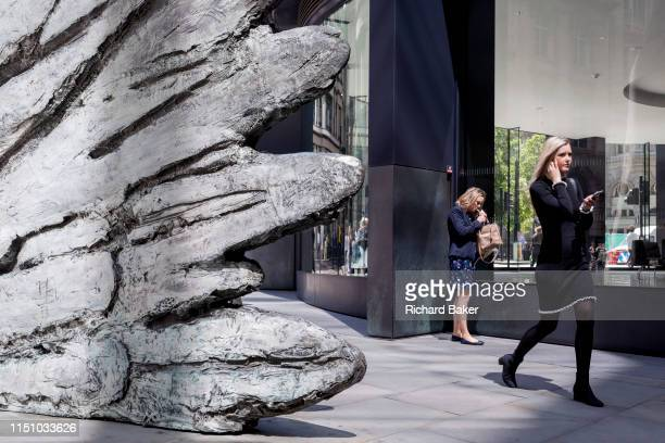 Lady lights a cigarette as a younger, healthier woman walks past the sculpture entitled 'City Wing' on Threadneedle Street in the City of London, the...
