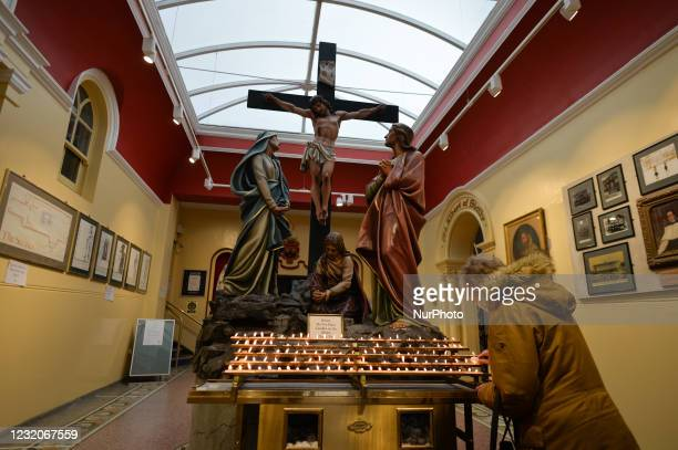Lady loghts a candle at the entrance to Whitefriar Church in Dublin, on Good Friday 2021, during level 5 COVID-19 lockdown. On Friday, 2 April 2021,...