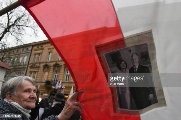 A lady look at an image of President Lech Kaczynski and his wife Maria Kaczynski seen attached to a Polish flag outside of Katyn Cross monument near...