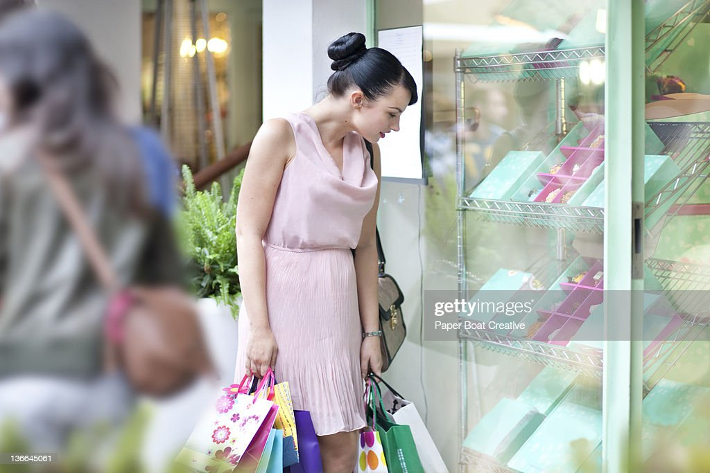 lady looking at colorful desserts by the window : Stock Photo