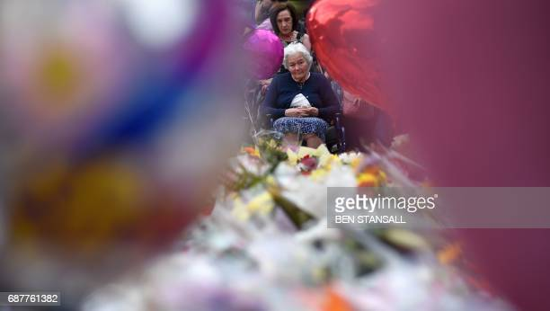 A lady looks at flowers in St Ann's Square in Manchester northwest England on May 24 placed in tribute to the victims of the May 22 terror attack at...