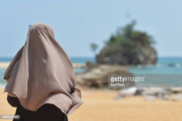 A lady looks at Kemasek Beach that lies on the main route from Kuala Terrengganu to Kemaman with an interesting rock formations seen during the...