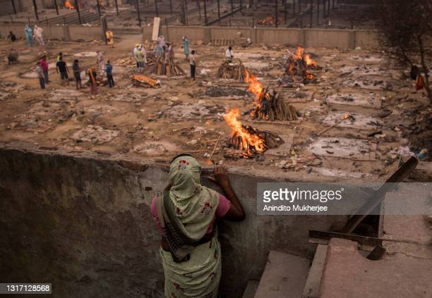 Lady looks at the burning funeral pyres of the patients who died of the Covid-19 coronavirus from her house near a makeshift crematorium on May 09,...
