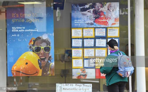 Lady looks at the Hays Travel Agents holiday deals in their shop window on May 12, 2021 in Newcastle-Under-Lyme, England.