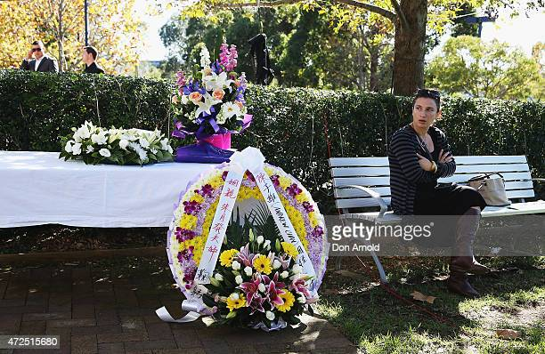 A lady looks on as flowers are placed in tribute before the funeral service for executed Bali nine member Andrew Chan at Hillsong Church Baulkham...