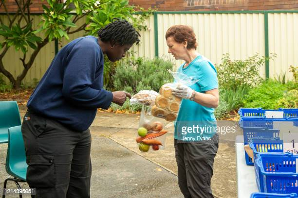 A lady looks on as volunteer Kerin Brown hands her food items at St Paul's Anglican Church in Burwood on March 24 2020 in Sydney Australia The Parish...