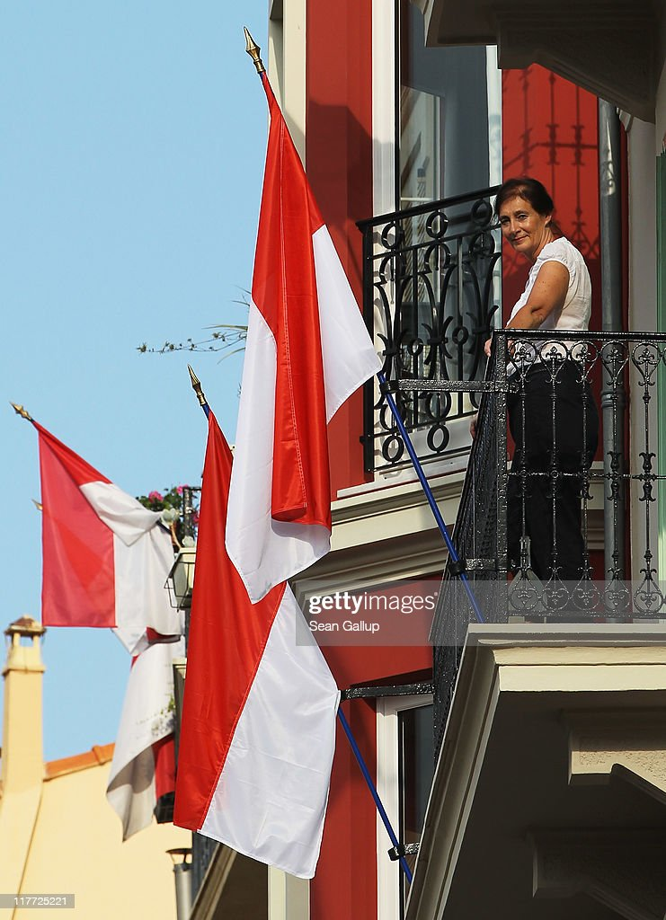 A lady looks out from her balcony ahead of the Royal Wedding of Prince Albert II of Monaco to Charlene Wittstock on June 30, 2011 in Monaco. The civil ceremony will take place in the Throne Room of the Prince's Palace of Monaco on July 1, followed by a religious ceremony to be conducted in the main courtyard of the Palace on July 2. With her marriage to the head of state of Principality of Monaco, Charlene Wittstock will become Princess consort of Monaco and gain the title, Princess Charlene of Monaco. Celebrations including concerts and firework displays are being held across several days, attended by a guest list of global celebrities and heads of state.