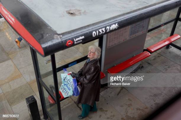 A lady looks up at due bus times at a bus stop in central London on 19th October 2017 in London England