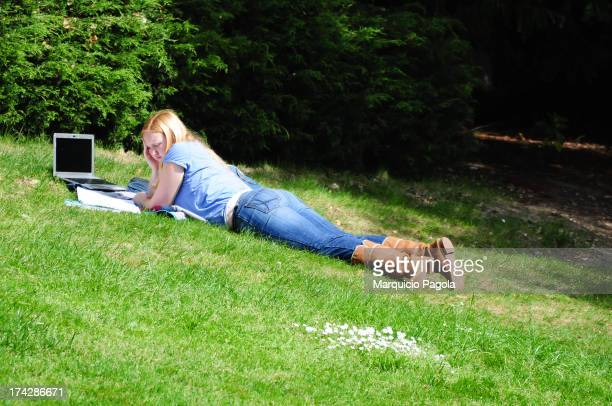 Lady lying in the grass, is studying under the sun, using a laptop and reading a book. She is wearing a skyblue blouse, a par of jeans and brown...