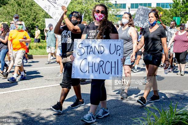 A lady marches to Town Point Park with a sign that says Stand Up Church during the City Collective Prayer March on June 7 in Norfolk VA The event...