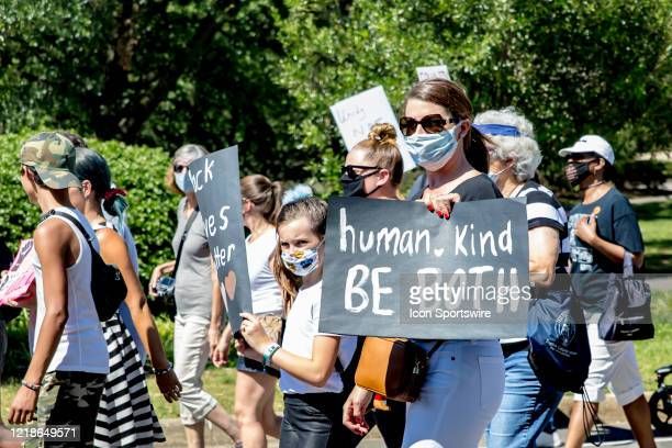 A lady marching down Waterside Drive displays a sign which says Human kind BE BOTH during the City Collective Prayer March on June 7 in Norfolk VA...