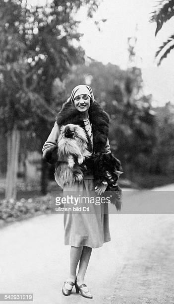 Lady Mortimer Davis mit ihrem Schosshund auf dem Arm im Garten ihrer Villa in Cannes 1928