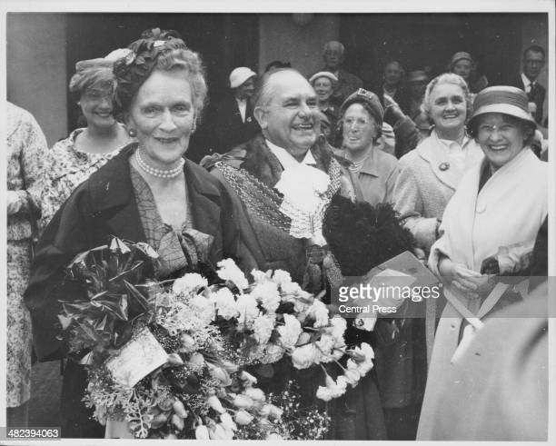 Lady Nancy Astor with Lord Mayor Washbourn, holding a large bouquet of flowers as she is greeted by well-wishers, following the ceremony to make her...
