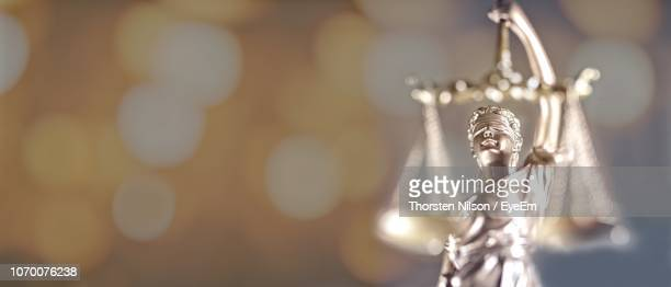 lady of justice against illuminated lights - lady justice stock pictures, royalty-free photos & images