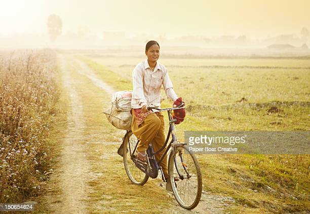 lady on a bicycle going to work in chitwan nepal - terai stock pictures, royalty-free photos & images