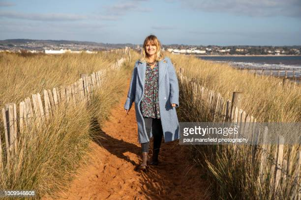 lady on devon coastline - coat stock pictures, royalty-free photos & images