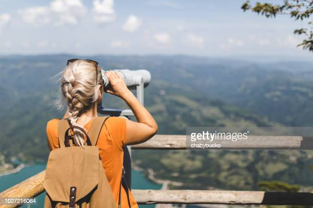 lady on viewpoint looking nature trough binoculars - binoculars stock pictures, royalty-free photos & images