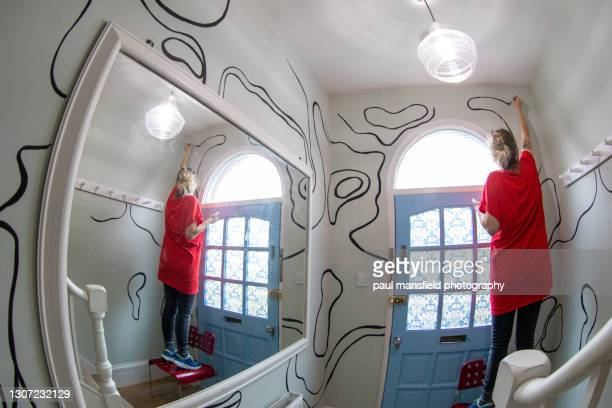 lady painting mural in hallway - art stock pictures, royalty-free photos & images