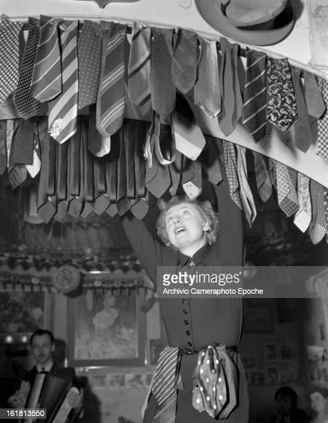 Lady Patachou hangs the tie down the door frame Paris 1950s