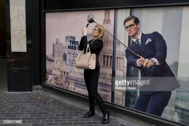 A lady pauses to take a picture of the nearby Lloyds Building next to a closed shop poster featuring a businessman enjoying leisure time on the golf...