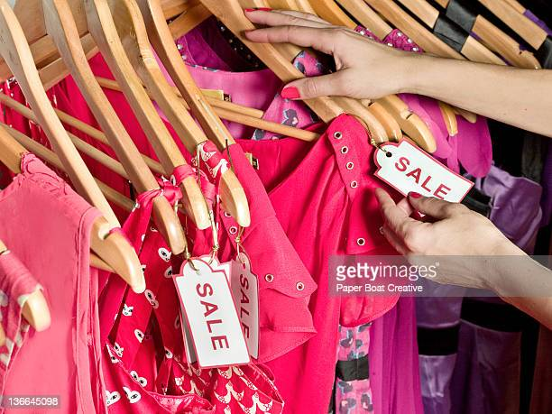 lady picking out dresses with a sale tag on it - pink dress stock photos and pictures