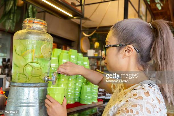 Lady pouring water from a water dispenser