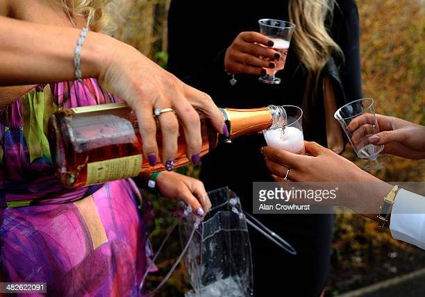 A lady pours pink champagne for her friends on Ladies Day at Aintree racecourse on April 04 2014 in Liverpool England