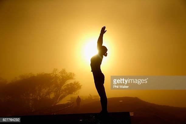 Lady practices yoga on the summit of Mt Eden as the sun struggles to shine through a blanket of fog over Auckland City on May 4, 2016 in Auckland,...