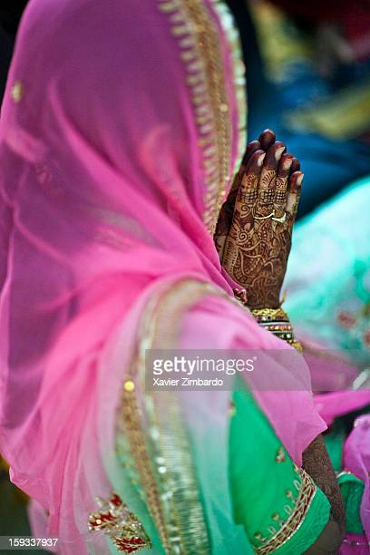 A lady praying in front of the family altar with her hands colored by the red 'mehendi' on February 16 2011 at Jhala House in Pali Marwar Rajasthan...
