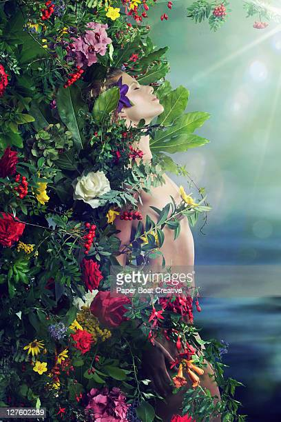 lady pressed against a wall of flowers and leaves