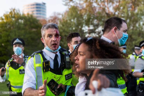 Lady pushes back a bleeding police officer during clashes after demonstrations at Hyde Park. People called online to a flash mob-style mass gathering...
