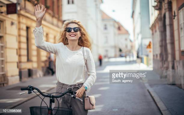 lady, die ein fahrrad schieben - winken stock-fotos und bilder