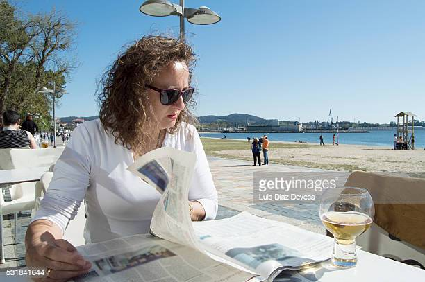 Lady reading the newspaper and having a beer in the terrace