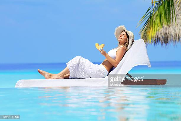 Lady relaxing in the chaise lounge on a exotic resort.